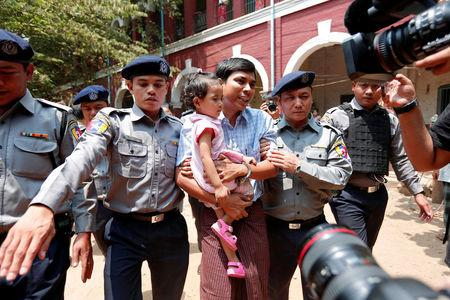Detained Reuters journalist Kyaw Soe Oo holding his daughter is escorted by police  after a court hearing in Yangon, Myanmar March 28, 2018. REUTERS/Stringer