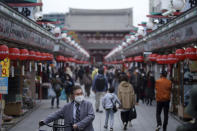 People wearing protective masks to help curb the spread of the coronavirus walk through a shopping arcade at the Asakusa district Tuesday, Nov. 24, 2020, in Tokyo. The Japanese capital confirmed more than 180 new coronavirus cases on Tuesday. (AP Photo/Eugene Hoshiko)