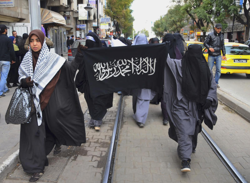 FILE - This Friday Jan. 20, 2012, file photo shows Tunisian Salafist women demonstrating near the French embassy in Tunis, Tunisia, in support of a Muslim woman who was fined in France for wearing a niqab Muslim veil. An emerging movement of believers known as Salafis has seemingly appeared out of thin air _ and prompted fears of a culture war in this North African country of 10 million. Since the overthrow of President Zine El Abidine Ben Ali in January 2011 unleashed a string of Arab uprisings, Islam has blossomed in Tunisia in a way it wasn't allowed to do for half a century.Sign reads: Allah is the Only God, and Mahommed is his Prophet. (AP Photo/Hassene Dridi, File)