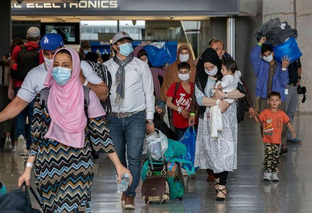 PHOTO: Families evacuated from Kabul, Afghanistan, walk through the terminal to board a bus after they arrived at Washington Dulles International Airport, in Chantilly, Va., on Sep. 1, 2021. (Gemunu Amarasinghe/AP)