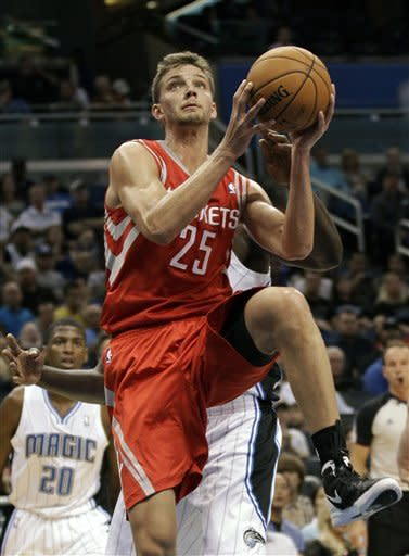Houston Rockets' Chandler Parsons (25) goes in for a shot in front of Orlando Magic's DeQuan Jones (20) and Andrew Nicholson during the first half of an NBA preseason basketball game, Friday, Oct. 26, 2012, in Orlando, Fla. (AP Photo/John Raoux)