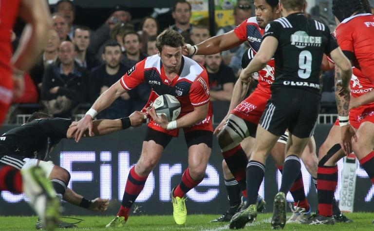 Toulouse's Maxime Medard (2nd-L) holds the ball during their match against Brive on March 11, 2017 in Brive, western France