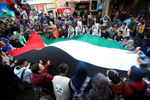 <p>Students hold a Palestinian flag inside the Ain el-Hilweh refugee camp near Sidon, southern Lebanon, Dec. 6, 2017. (Photo: Ali Hashisho/Reuters) </p>