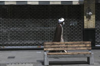 A cleric walks past a closed shop of Tehran's Grand Bazaar, Iran, Saturday, April 10, 2021. Iran on Saturday imposed partial lockdown on businesses in major shopping centers as well as intercity travels through personal cars in major cities including capital Tehran as it struggles with the worst outbreak of the coronavirus in the Mideast region. (AP Photo/Vahid Salemi)