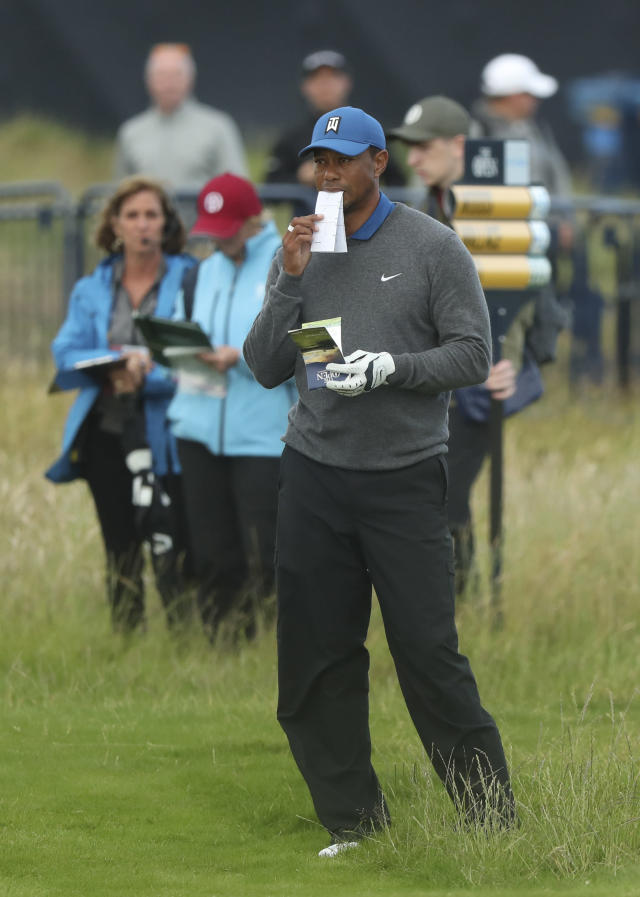 Tiger Woods of the United States looks at his playing guides on the 18th fairway during the first round of the British Open Golf Championships at Royal Portrush in Northern Ireland, Thursday, July 18, 2019.(AP Photo/Jon Super)