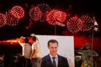 Supporters of of Syria's President Bashar al-Assad celebrate after the results of the presidential election announced that he won a fourth term in office, in Damascus