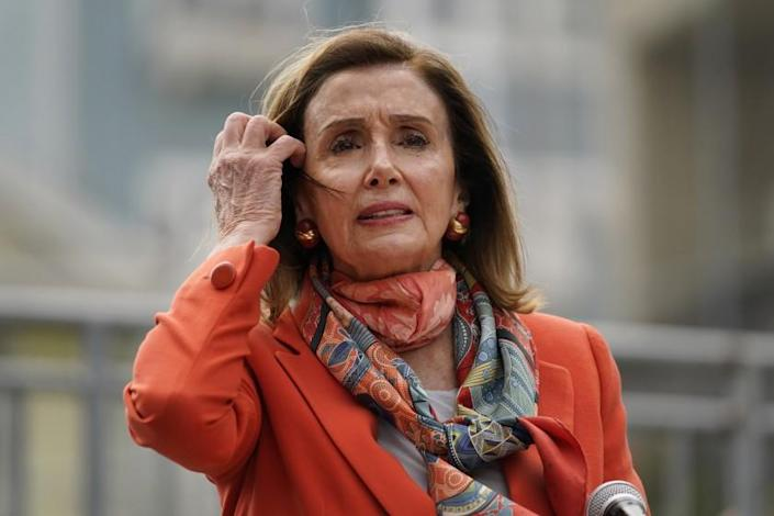 House Speaker Nancy Pelosi pulls back her hair while speaking about her visit to a hair salon.
