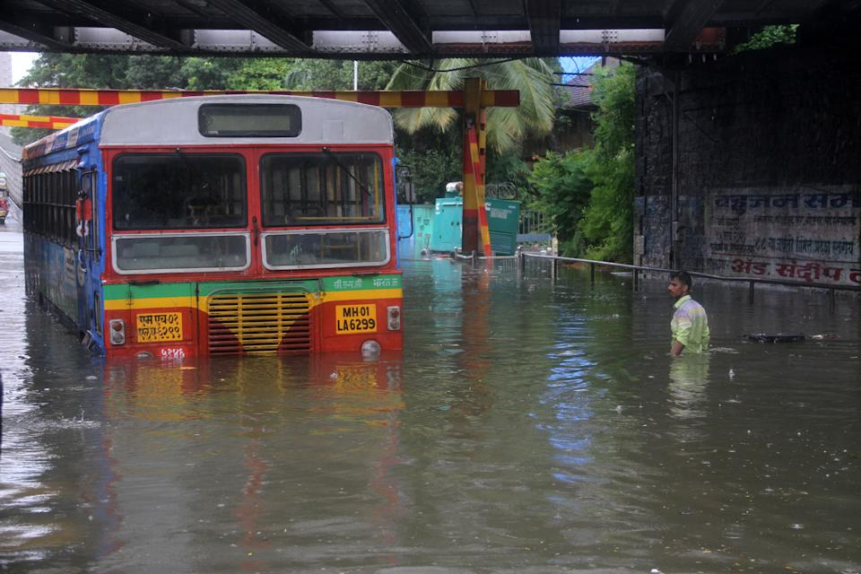 MUMBAI, INDIA - AUGUST 4: A vehicle and a man make their way through a flooded road due to heavy monsoon rain in Mumbai, India on August 4, 2020. (Photo by Imtiyaz Shaikh/Anadolu Agency via Getty Images)