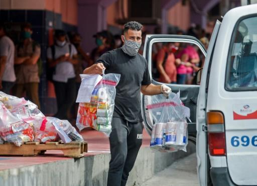 A worker loads online purchases on a van to be delivered, outside a pick up center in Havana, on June 17, 2020