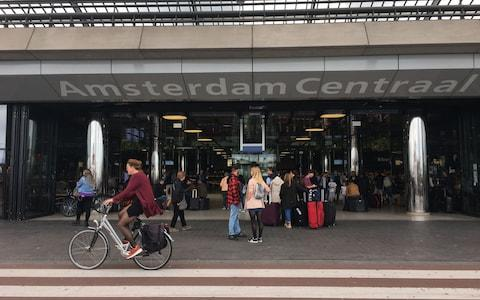 Passengers are pictured outside the Central Railway Station in Amsterdam  - Credit:  GERMAIN MOYON/AFP