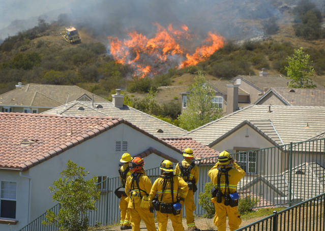 Firefighters from Glendale, Calif., and Pasadena, Calif., stand watch as bulldozers clear a firebreak near a wildfire burning along a hillside near homes in Thousand Oaks, Calif., Thursday, May 2, 2013. A Ventura County Fire Department spokeswoman said the blaze that broke out Thursday morning near Camarillo and Thousand Oaks, 50 miles west of Los Angeles, had spread to over 6,500 acres, forcing evacuations of nearby neighborhoods. (AP Photo/Mark J. Terrill)