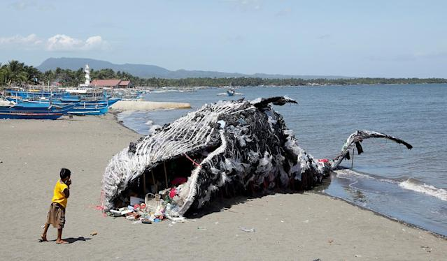 <p>A boy looks at a whale shaped art installation that is made of plastic and trash made by environmental activist group Greenpeace Philippines, lying along the shore in Naic, Cavite, in the Philippines May 12, 2017. (Photo: Erik De Castro/Reuters) </p>