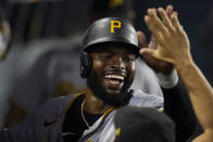 Pittsburgh Pirates' Gregory Polanco (25) is high-fived by teammates in the dugout after scoring a run during the sixth inning of a baseball game against the Los Angeles Dodgers Monday, Aug. 16, 2021, in Los Angeles. (AP Photo/Marcio Jose Sanchez)