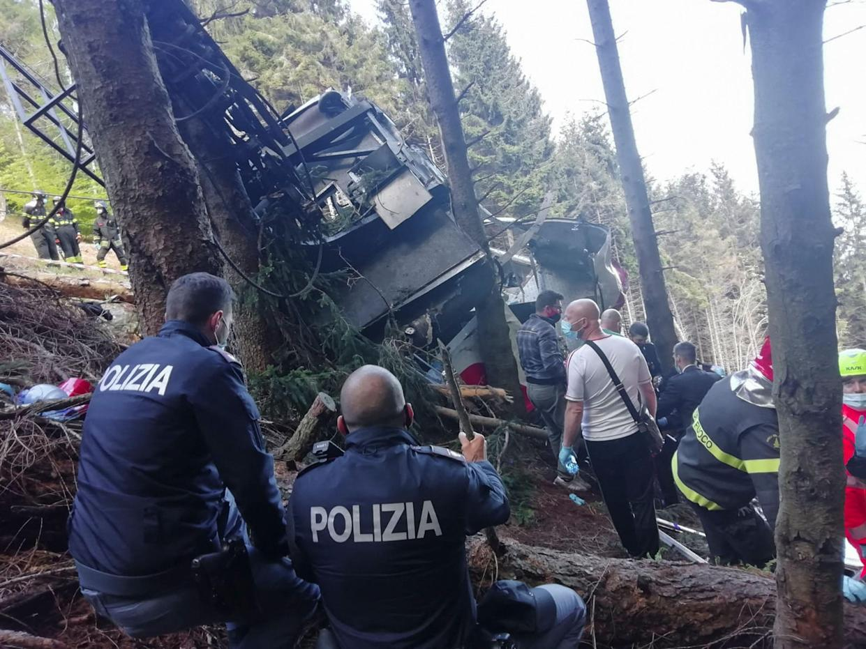 Italian State Police officers and rescuers by a cable car that crashed to the ground in the resort town of Stresa on the shores of Lake Maggiore in the Piedmont region.