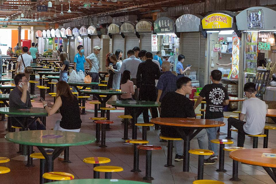 People queueing for food at the Maxwell Food Centre on 7 April 2020, the first day of Singapore's month-long circuit breaker period. (PHOTO: Dhany Osman / Yahoo News Singapore)