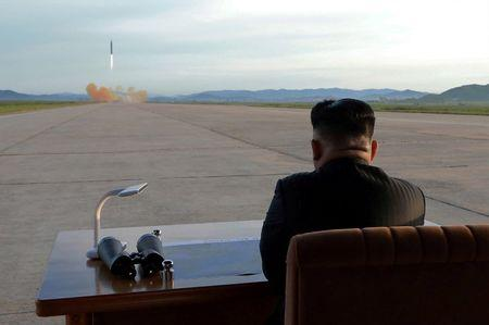 North Korean leader Kim Jong Un watches the launch of a Hwasong-12 missile in this undated photo released by North Korea's KCNA