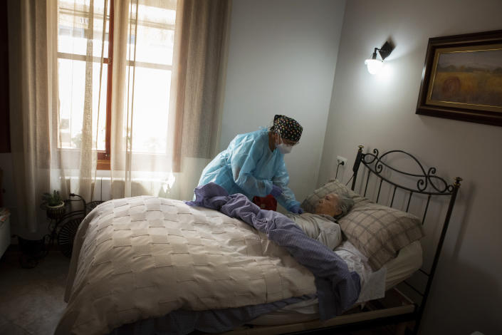 Nurse Pilar Rodríguez administers the COVID-19 vaccine to her patient Margarita Serra Crespi, 93, at her home in the town of Sa Pobla on the Spanish Balearic Island of Mallorca, Spain, Friday, April 30, 2021. Margarita who suffers from senile dementia and has been bedridden for more than two years, receives regular visits from her caregiver and nurse Pilar, one of three nurses in the town of Sa Pobla in the interior of the island and in nearby villages.(AP Photo/Francisco Ubilla)