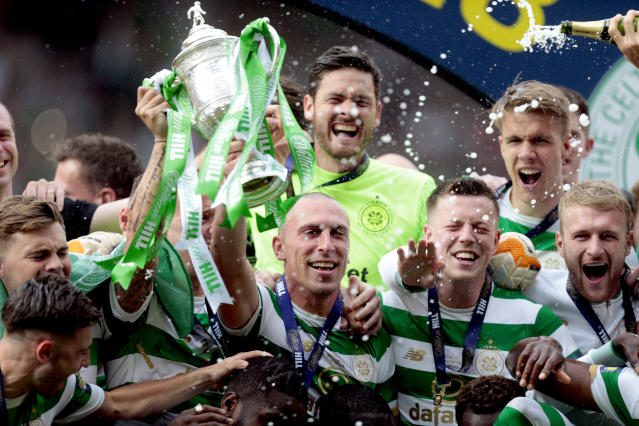Celtic's Scott Brown, center, lifts the trophy after winning the Scottish Cup soccer final match, at Hampden Park, Glasgow, Scotland, Saturday, May 19, 2018. (Graham Stuart/PA via AP)