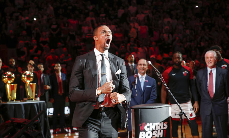 Former Miami Heat player Chris Bosh reacts at the team's retirement of his jersey at halftime of an NBA game between the Heat and the Orlando Magic, Tuesday, March 26, 2019, in Miami. Heat president Pat Riley is at right and left of Riley is Miami Heat guard Dwyane Wade. Bosh played 13 seasons, the first seven in Toronto and the last six in Miami. He averaged 19.2 points and 8.5 rebounds, was an All-Star 11 times and won two championships.(AP Photo/Joe Skipper)
