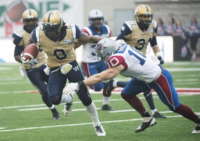 Winnipeg Blue Bombers' Johnny Sears, left, is tackled by Montreal Alouettes' Marc-Olivier Brouillette during first half CFL football action in Montreal, Monday, October 14, 2013. THE CANADIAN PRESS/Graham Hughes