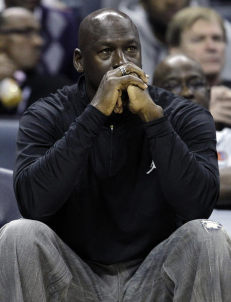 FILE - In this Jan. 16, 2012, file photo, Charlotte Bobcats owner Michael Jordan watches during the first half of an NBA basketball game between the Bobcats and the Cleveland Cavaliers in Charlotte, N.C. Jordan's No. 23 has long been synonymous with greatness. By Thursday night, that number could have a completely different meaning. If Jordan's Charlotte Bobcats lose to the New York Knicks, it will be their 23rd consecutive loss and they'll finish the season with the worst winning percentage in NBA history. (AP Photo/Chuck Burton, File)