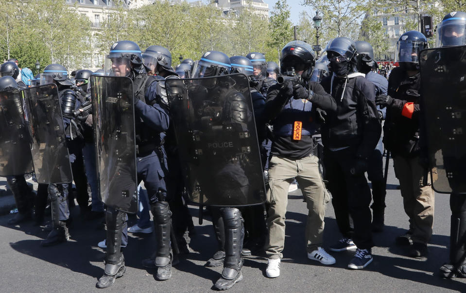 Police move in to confront protestors at the Place de Republique during a yellow vest demonstration in Paris, Saturday, April 20, 2019. French yellow vest protesters are marching anew to remind the government that rebuilding the fire-ravaged Notre Dame Cathedral isn't the only problem the nation needs to solve. (AP Photo/Michel Euler)
