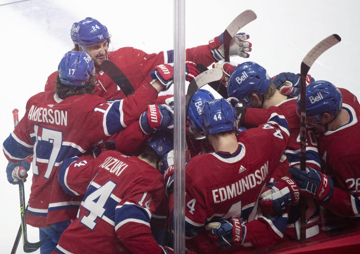 Players from the Montreal Canadiens celebrate Cole Caufield's goal against the Toronto Maple Leafs during overtime NHL hockey game action in Montreal, Monday, May 3, 2021. (Graham Hughes/The Canadian Press via AP)