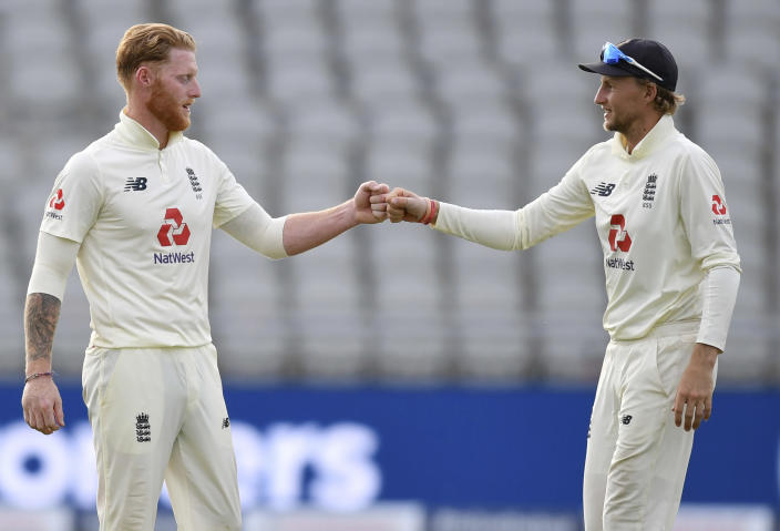 England's captain Joe Root, right, fist bumps with teammate Ben Stokes at the end of the third day of the first cricket Test match between England and Pakistan at Old Trafford in Manchester, England, Friday, Aug. 7, 2020. (Dan Mullan/Pool via AP)