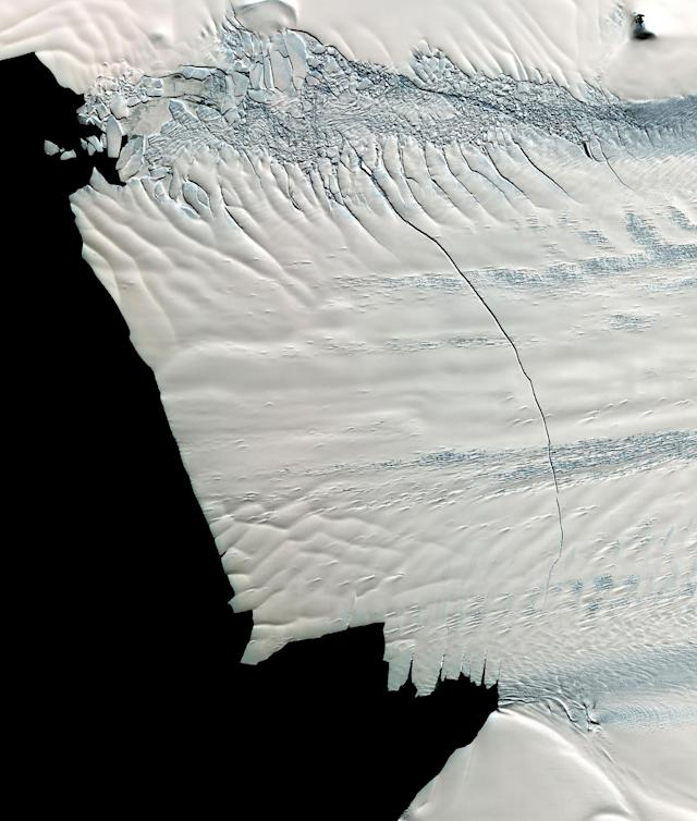 <p>An aerial view of a massive crack across the Pine Island Glacier, Nov. 13, 2011. In mid-October 2011, NASA scientists working in Antarctica discovered a massive crack across the Pine Island Glacier, a major ice stream that drains the West Antarctic Ice Sheet. Extending for 19 miles (30 kilometers), the crack was 260 feet (80 meters) wide and 195 feet (60 meters) deep. Eventually, the crack will extend all the way across the glacier, and calve a giant iceberg that will cover about 350 square miles (900 square kilometers). (Photo: NASA/GSFC/METI/ERSDAC/JAROS, and U.S./Japan ASTER Science Team) </p>