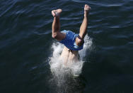 A person dives into the water from a pedestrian bridge at Lake Union Park into the water during a heat wave hitting the Pacific Northwest, Sunday, June 27, 2021, in Seattle. Yesterday set a record high for the day with more record highs expected today and Monday. (AP Photo/John Froschauer)