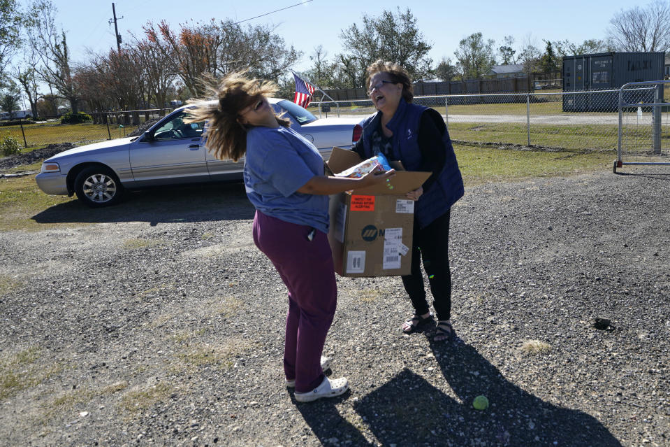 Katelyn Smith, left, reacts after a well-wisher brought her Christmas presents for her one-year-old son, on Christmas Eve in the aftermath of Hurricane Laura and Hurricane Delta, in Lake Charles, La., Thursday, Dec. 24, 2020. Katelyn, her fiancé and son are living in a loaned camper after their family home and possessions were destroyed by the back-to-back storms. (AP Photo/Gerald Herbert)