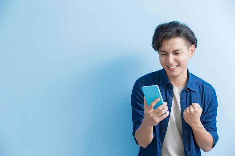 A young man uses a smartphone.
