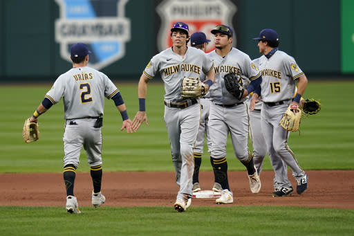 Members of the Milwaukee Brewers including Luis Urias (2) and Christian Yelich, second from left, celebrate a 3-0 victory over the St. Louis Cardinals in the first game of a baseball doubleheader Friday, Sept. 25, 2020, in St. Louis. (AP Photo/Jeff Roberson)