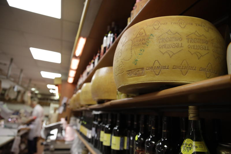 Wheels of parmesan cheese are stored in a deli in Rome, Thursday, Oct. 3, 2019. The U.S. had prepared for Wednesday's ruling and already drawn up lists of the dozens of goods it would put tariffs on. They include EU cheeses, olives, and whiskey, as well as planes, helicopters and aircraft parts in the case _ though the decision is likely to require fine-tuning of that list if the Trump administration agrees to go for the tariffs. (AP Photo/Alessandra Tarantino)