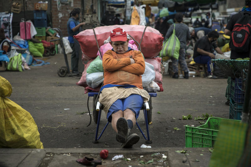 Porter Fernando Anaya, who begins his workday at 4 a.m., takes a nap as he takes a break from transporting vegetables, in La Parada market in La Victoria district, in Lima, Peru, Tuesday, June 23, 2020. With hundreds of millions relying on such markets for their food and livelihoods, officials are debating whether and how they can operate safely amid the new coronavirus pandemic. (AP Photo/Rodrigo Abd)