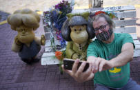 A man takes a selfie with a statue of the comic strip character Mafalda created by Argentine cartoonist Joaquin Salvador Lavado, who was better known as Quino, in Buenos Aires, Argentina, Wednesday, Sept. 30, 2020. Lavado passed away on Wednesday, Sept. 30, 2020, according to his editor Daniel Divinsky who announced it on social media. He was 88.(AP Photo/Victor R. Caivano)