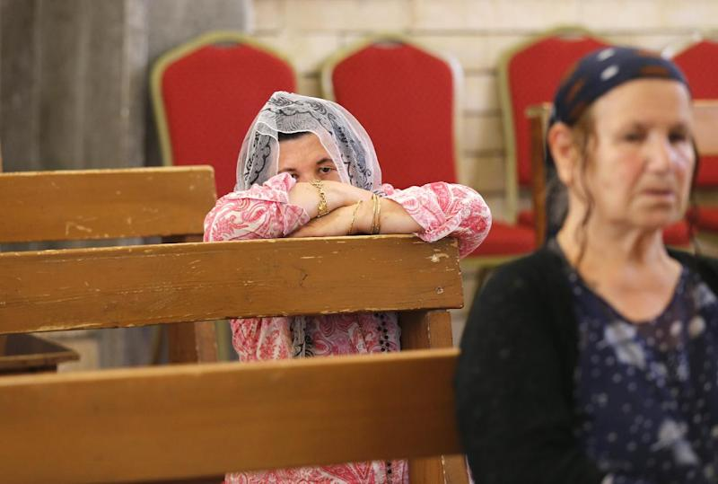An Iraqi Christian fleeing the violence in the towns of Qaraqush and Bartala, both east of the city of Mosul, prays at the Saint George church on July 1, 2014 in Abil, Iraq (AFP Photo/Karim Sahib )