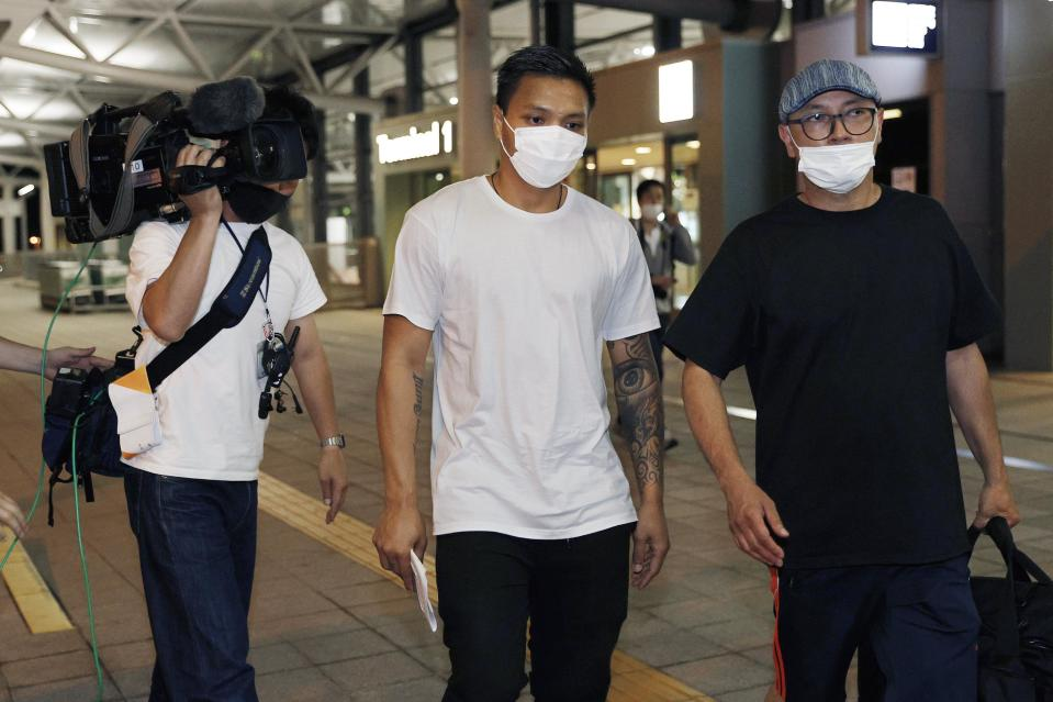 Pyae Lyan Aung, center, a substitute goalkeeper of the Myanmar national team who raised a three-finger salute during a qualifying match for the 2022 World Cup in late May, arrives at Kansai International Airport in Osaka Prefecture, Japan on Thursday June 17, 2021. Pyae Lyan Aung has refused to return home and is seeking asylum, a request the government was considering taking into account unrest in his country following a coup.(Kyodo News via AP)