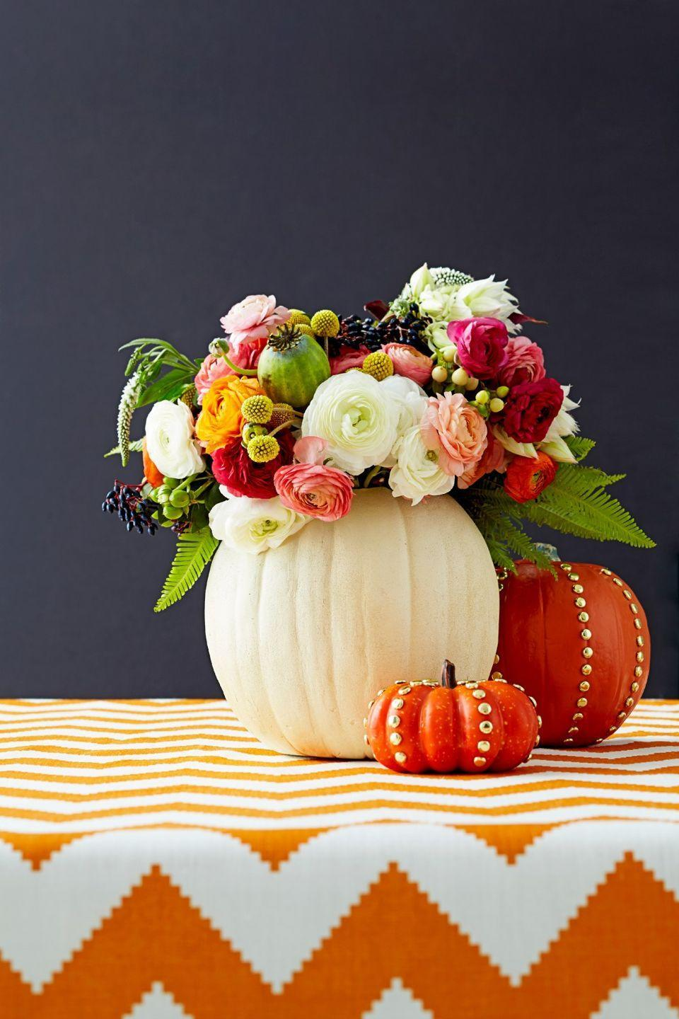 <p>Put your blooms center stage by hiding a water-filled vase inside a hollow pumpkin. Punch it up by adding shiny gold tacks along the ridges.</p>