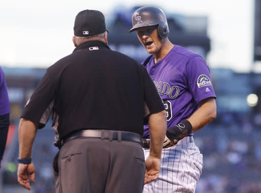 Colorado Rockies' DJ LeMahieu, right, argues with first base umpire Fieldin Culbreth after he called out LeMahieu when he was caught in a rundown while trying to advance from first to second base in the first inning of a baseball game against the Monday, Sept. 10, 2018, in Denver. (AP Photo/David Zalubowski)
