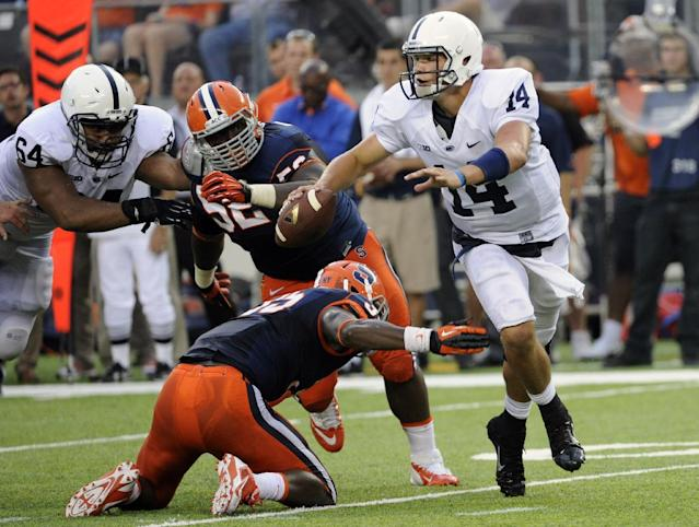 Penn State quarterback Christian Hackenberg (14) slips away from Syracuse linebacker Dyshawn Davis and nose tackle Eric Crume (52) during the fourth quarter of an NCAA college football game Saturday, Aug. 31, 2013, in East Rutherford, N.J. Penn State won 23-17. (AP Photo/Bill Kostroun)