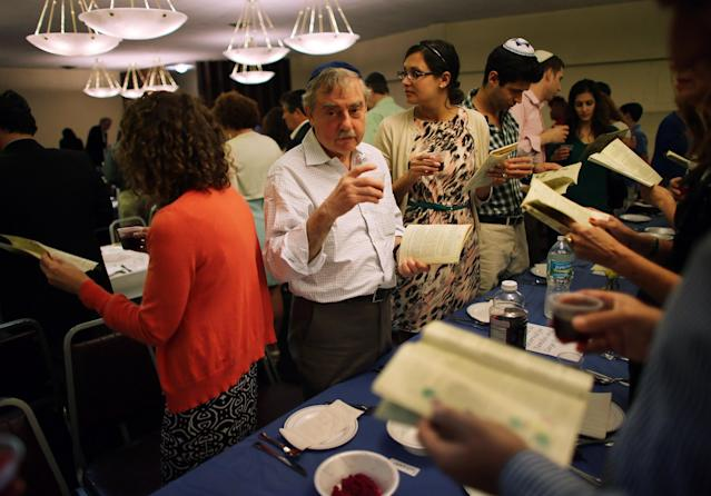 MIAMI BEACH, FL - MARCH 25: Garry Shomair and others drink a glass of wine during a community Passover Seder at Beth Israel synagogue on March 25, 2013 in Miami Beach, Florida. The community Passover Seder that served around 150 people has been held for the past 30 years and is welcome to anyone in the community that wants to commemorate the emancipation of the Israelites from slavery in ancient Egypt. (Photo by Joe Raedle/Getty Images)
