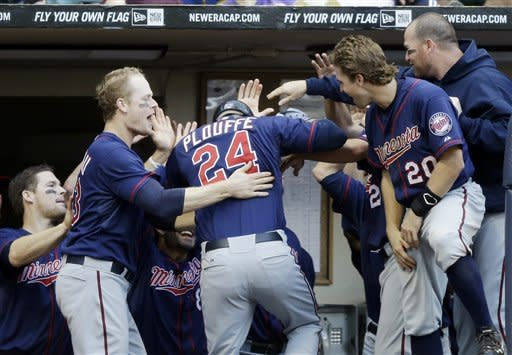 Teammates congratulate Minnesota Twins' Trevor Plouffe after his home run during the 11th inning of a baseball game against the Milwaukee Brewers Saturday, May 19, 2012, in Milwaukee. (AP Photo/Morry Gash)