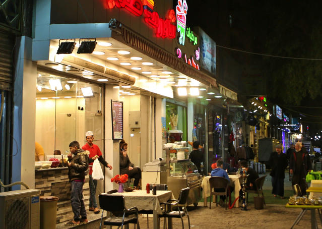 In this Feb. 14, 2019 photo, shops and restaurants are open late at night in Baghdad, Iraq. For the first time in years, Iraq is not at war. The defeat of the Islamic State group in late 2017 after a ruinous four-year conflict has given the population a moment of respite, and across the capital Baghdad there is a guarded sense of hope. (AP Photo/Khalid Mohammed)