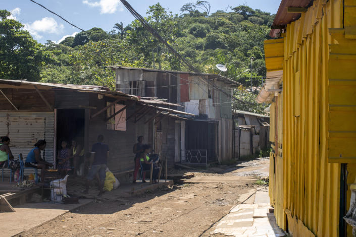 People, some of them from Haiti, sit outside their homes in the slum district of Mont Baduel, in Cayenne, French Guiana, Friday, July 10, 2020. France's most worrisome virus hotspot is in fact on the border with Brazil - in French Guiana, a former colony where health care is scarce and poverty is rampant. The pandemic is exposing deep economic and racial inequality in French Guiana that residents say the mainland has long chosen to ignore. (AP Photo/Pierre Olivier Jay)