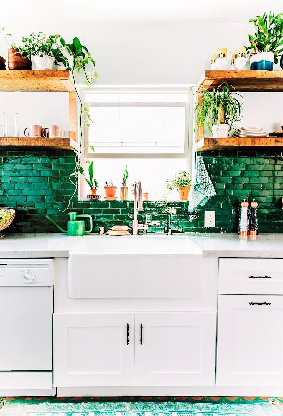 <p>Emerald-colored tiles play off of this cozy kitchen's potted plants, while white cabinets and wood shelving add to its charm. </p>