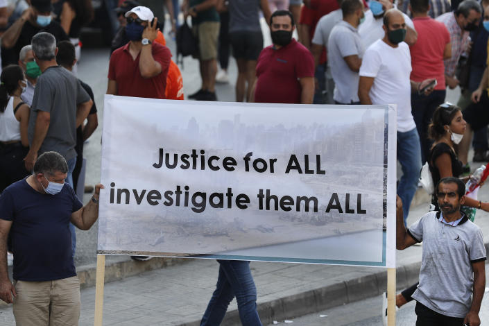 """FILE - In this Aug. 31, 2020 file photo, Lebanese supporters of President Michel Aoun hold a banner during a protest calling for """"truth and justice"""" in relation to the Aug. 4 explosion that devastated Beirut port and parts of the Lebanese capital, in Beirut, Lebanon. A public feud in recent weeks among prosecutors has starkly demonstrated how Lebanon's system of sectarian factions is paralyzing Lebanon's judicial system and snarling attempts to root out corruption. (AP Photo/Hussein Malla, File)"""