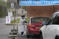 FILE - In this Oct. 21, 2020, file photo, medical personnel prepare to administer a COVID-19 swab at a drive-through testing site in Lawrence, N.Y. The United States is approaching a record for the number of new daily coronavirus cases in the latest ominous sign about the disease's grip on the nation. (AP Photo/Seth Wenig, File)