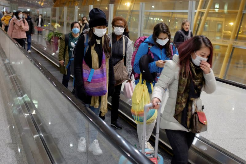 People wear face masks as they arrive at Beijing Capital International Airport in Beijing