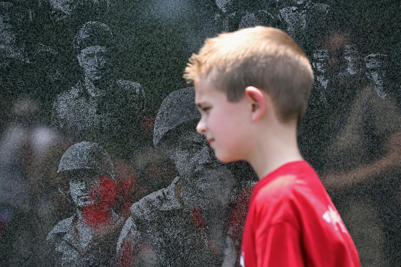 "A military child grieving the death of a parent visits the Korean War Memorial as part of the TAPS ""Good Grief Camp"" on May 26, 2012 in Washington, DC. Five hundred military children and teens, most of whom lost a parent or sibling in the Afghan and Iraq wars, are attending the annual four-day ""Good Grief Camp"" in Arlington, Virginia and Washington, DC, which is run by TAPS (Tragedy Assistance Program for Survivors). The camp helps them learn coping skills and build relationships so they know they are not alone in the grief of their loved one. They meet others of their own age group, learn together and share their feelings, both through group activities and one-on-one mentors, who are all active duty or former military service members. Some 1,200 adults, most of whom are grieving parents and spouses, also attend the National Military Survival Seminar held concurrently with the children's camp. The TAPS slogan is ""Remember the Love. Celebrate the Life. Share the Journey.""  (Photo by John Moore/Getty Images)"